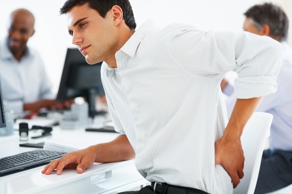 man hurting his lower back during a work meeting
