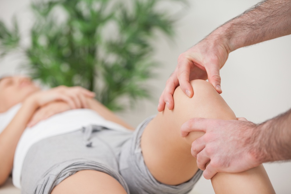 chiropractor in Boca Raton holding a patient's knee during chiropractic treatment for knee pain