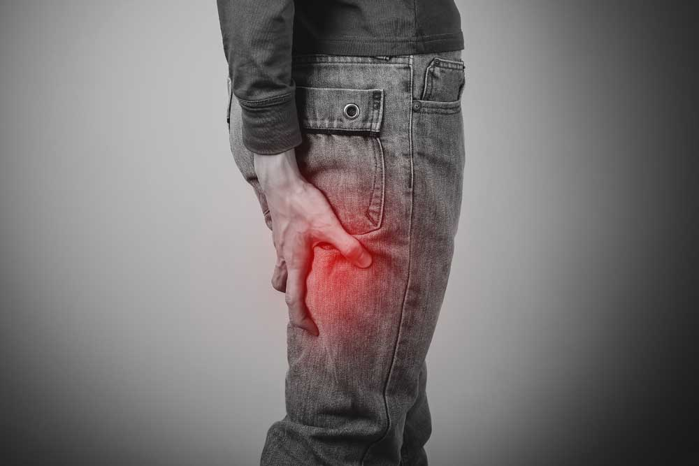 man holding the back of his leg from sciatica pain